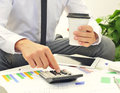 Young businessman using a calculator closeup of caucasian on table full of charts and cup of coffee in his hand Stock Image