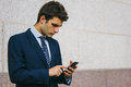Young businessman using his phone in a street photography of Stock Photography