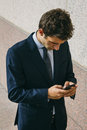 Young businessman using his phone in a street photography of Royalty Free Stock Images