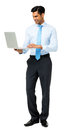 Young businessman using laptop full length of against white background vertical shot Royalty Free Stock Photography