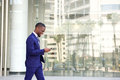 Young businessman walking and using cell phone Royalty Free Stock Photo