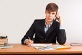 A young businessman writing document and calling by mobile phone in office Stock Images