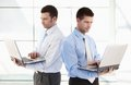 Young businessmen standing with laptop in hands Stock Images