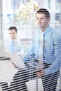 Young businessmen working in bright office behind blind Stock Photos