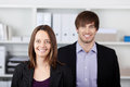 Young businesspeople standing in office portrait of businessman and businesswoman Royalty Free Stock Photo