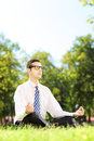 Young businessperson with eyeglasses meditating seated on a gras green grass in park Stock Image