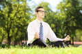 Young businessperson with eyeglasses meditating seated on a gras green grass in park Stock Photos