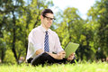 Young businessperson with glasses seated on a grass working on a green tablet in park Royalty Free Stock Photo