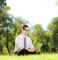Young businessperson on a grass working on a tablet with glasses sitting green and in park shot with tilt and shift lens Stock Images
