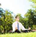 Young businessperson meditating seated on a grass in a park with eyeglasses Royalty Free Stock Photography