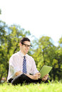 Young businessperson sitting on a grass and working on a tablet with glasses green in park Royalty Free Stock Image