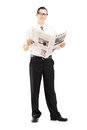 Young businessperson standing and reading a newspaper full length portrait of isolated against white background Royalty Free Stock Images