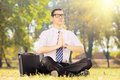 Young businessperson with tie doing yoga seated on grass in a pa exercise green park Royalty Free Stock Photography