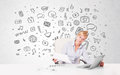 Young businesswoman with all kind of hand-drawn media icons in b Royalty Free Stock Photos