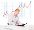 Young businesswoman calculating stock market with rising graph i beautiful in the background Royalty Free Stock Images