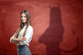 Young businesswoman is casting shadow of devil on rusty orange wall behind her. Royalty Free Stock Photo