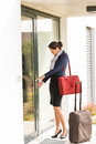 Young businesswoman locking door traveling luggage leaving Royalty Free Stock Photos