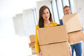 Young businesswoman with male colleague carrying cardboard boxes in new office Royalty Free Stock Photo