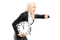 Young businesswoman running late with a wall clock in her hand isolated on white background Stock Photos