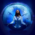 Young businesswoman sitting against blue background with clock interface Royalty Free Stock Photography