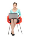 Young businesswoman sitting in chair with laptop Stock Photo