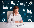 Young businesswoman sitting at desk with diagrams and statistics pretty Royalty Free Stock Images