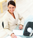 Young businesswoman sitting by desk with laptop Stock Images