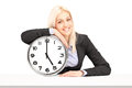Young businesswoman sitting with a wall clock Royalty Free Stock Photo