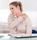 Young businesswoman suffering from shoulder pain at office Stock Image