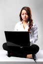 Young businesswoman working with a laptop while sitting on the f portrait of floor Royalty Free Stock Image