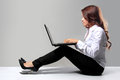 Young businesswoman working with a laptop while sitting on the f portrait of floor Stock Image