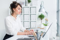 Young businesswoman working in office, typing, using computer. Concentrated woman searching information online Royalty Free Stock Photo