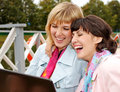 Young businesswomen with laptop outdoor women having conversation laughing fall Stock Photo