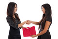 Young businesswomen shaking hands two mixed race business women in their early s passing a folder isolated on a white background Royalty Free Stock Images