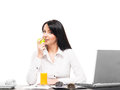 A young busineswoman eating an apple on white business woman has vegetarian lunch in office isolated Royalty Free Stock Photography