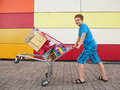 Young buyer boy with shopping trolley full of purchases in the street Royalty Free Stock Image