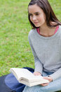 Young calm woman reading a book in a park while looking away