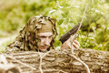 Young camouflaged military man in forest with gun Royalty Free Stock Photos
