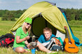 Young camping couple cooking meal outside tent Royalty Free Stock Images