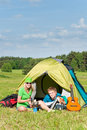 Young camping couple cooking meal outside tent Royalty Free Stock Photos