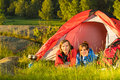 Young camping couple lying in tent resting and sunset countryside Royalty Free Stock Images