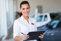 Young car saleswoman holding clipboard in showroom Royalty Free Stock Photos