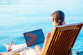Young carefree girl on a sun lounger with laptop Royalty Free Stock Photos