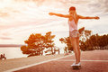 Young carefree woman riding a skateboard along the coast at sunset Royalty Free Stock Photography