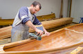 Young carpenter making constructing wooden canoe of his own desi Royalty Free Stock Photo