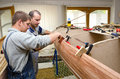 Young carpenters assembling new canoe of their design Royalty Free Stock Photo