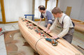 Young carpenters assembling new canoe of their own design Royalty Free Stock Photo