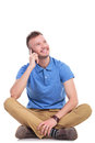 Young casual man on his phone looks away sitting the floor with legs crossed and talking the while looking up with a smile face Stock Image
