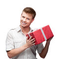 Young casual man hoding christmas gift caucasian holding red isolated on white background Stock Photo