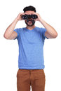 Young casual man is looking through binoculars and smiles on white background Stock Photos